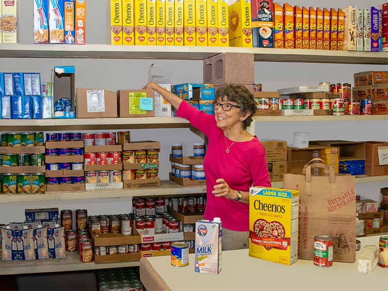 a woman smiling while stocking shelves with cans