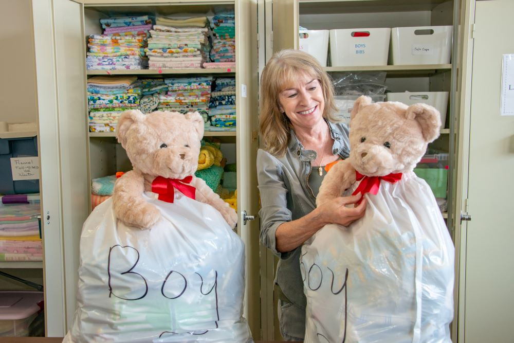 woman smiling at a teddy bear stuffed in the top of a layette bag