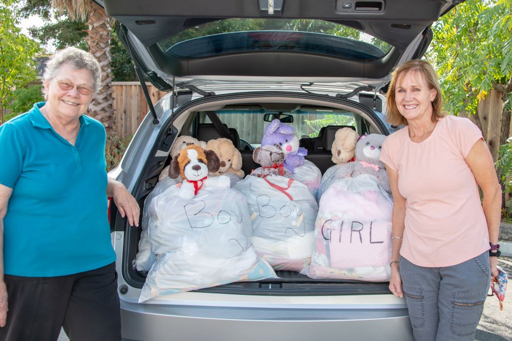 two women smiling at the camera with several layette bags packed in the trunk of a car